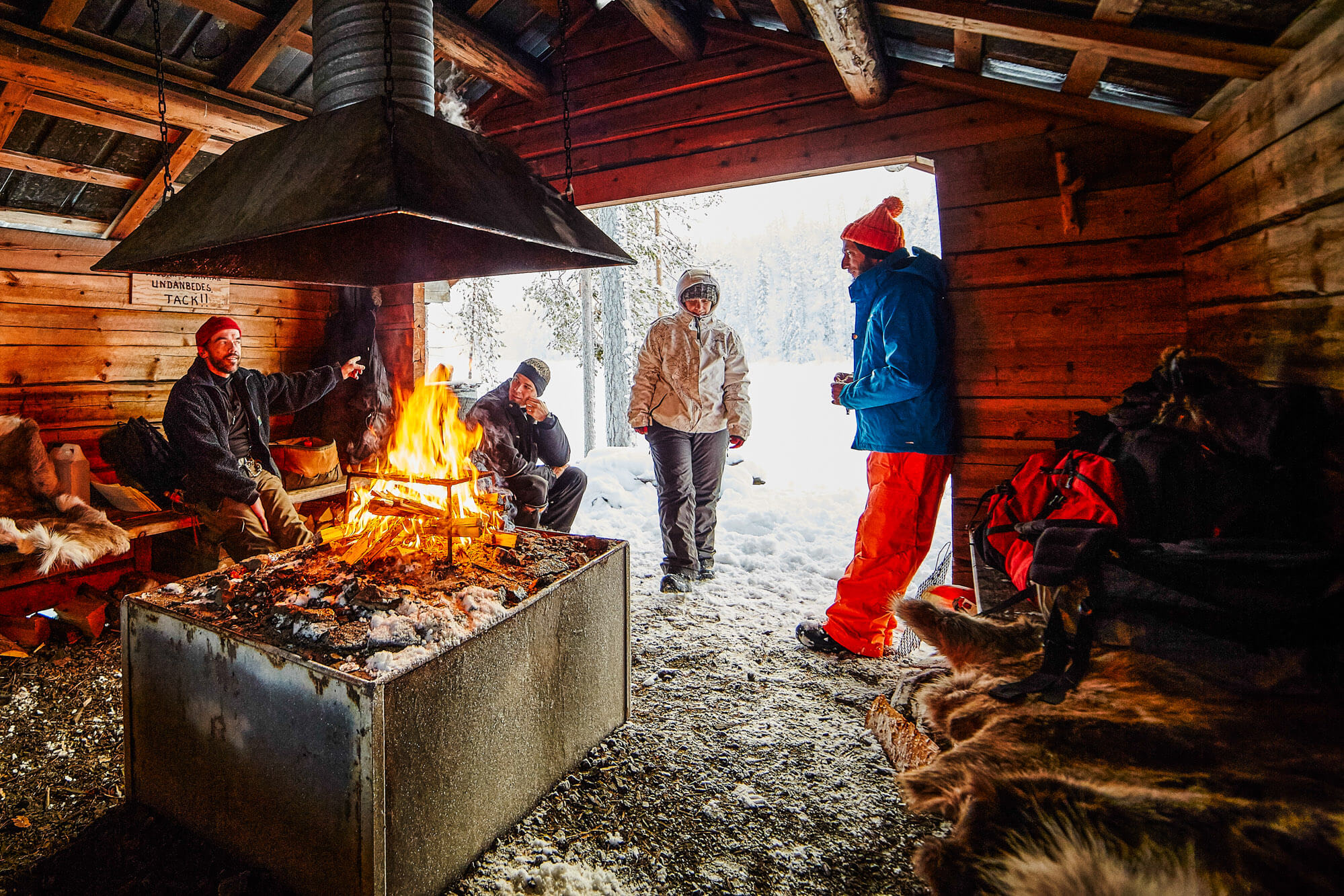 Lunch break around a wood fire in a cabin in Swedish Lapland