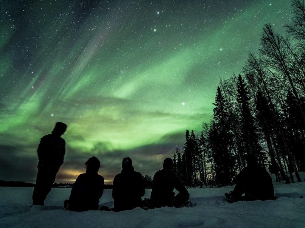 Des voyageurs admirent des aurores boréales sur le lac de Bredtrask en Laponie Suédoise