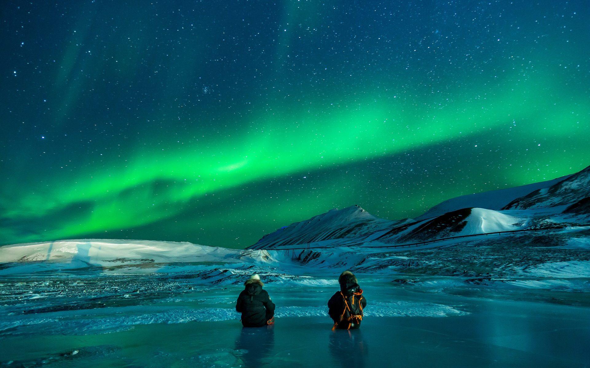 Deux voyageurs assis sur un lac gelé admirent une aurore boréale